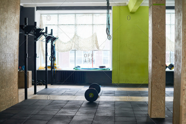 Empty spacious gym equipped with chin-up bars, gymnastic rings and barbell lying on black rubber mat
