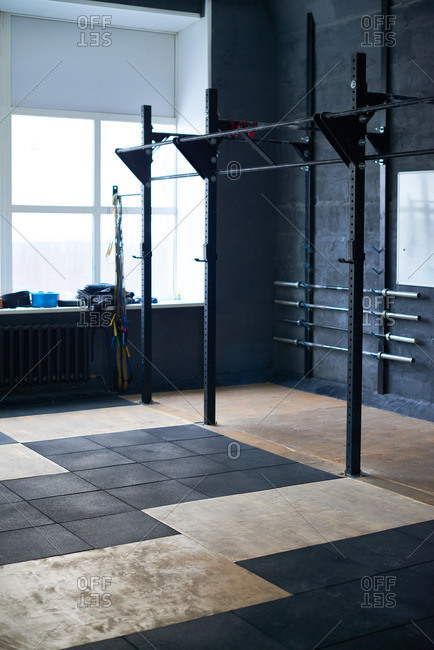 Modern roomy gym in dark tones equipped with different kinds of bars, skipping-ropes and black rubber mats for weightlifting