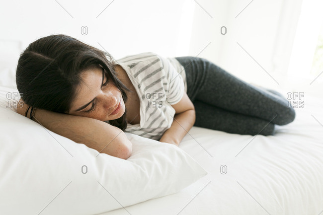 Young woman napping on a bed with white linens