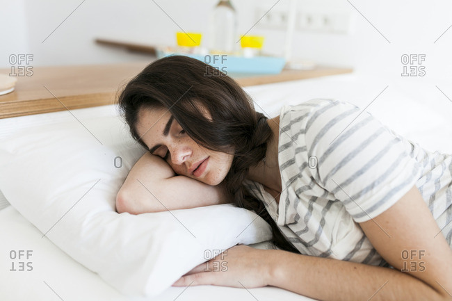 Young woman sleeping on a bed with white linens