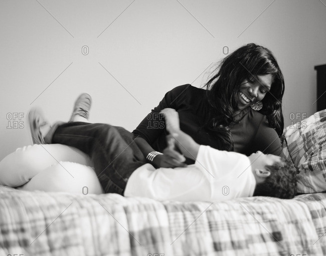 Mother tickling her son on a bed