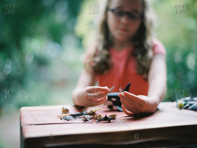 Little girl playing with small plastic toy animals