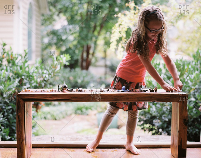 Young girl playing with small plastic toys on an outdoor table