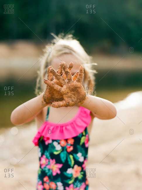 Girl holding her sandy hands in front of her face