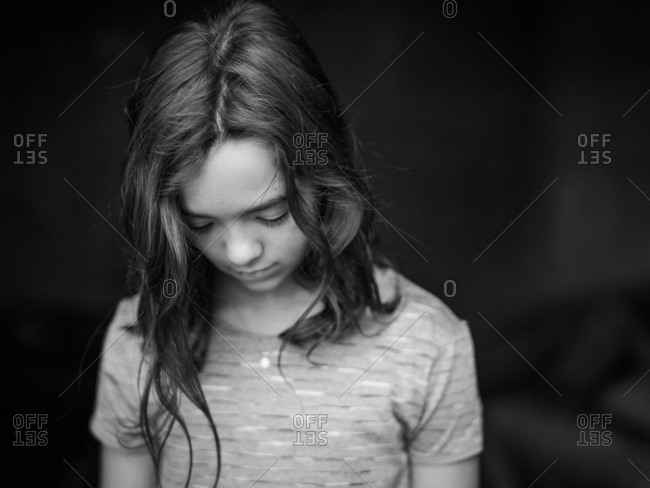 Portrait of a young girl looking down in black and white