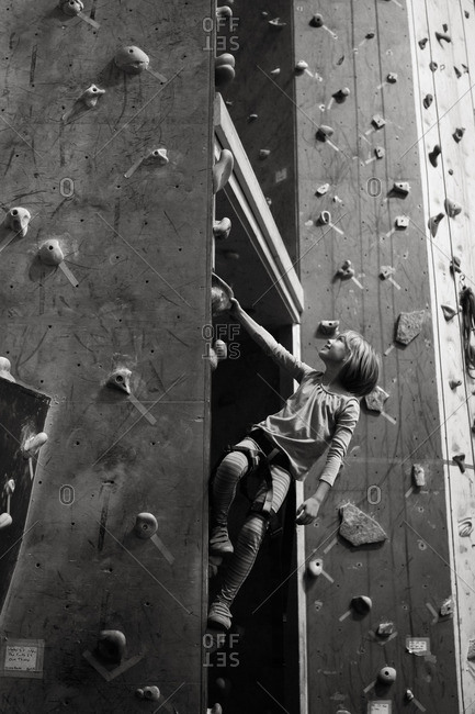 Young girl climbing up a rock wall in black and white