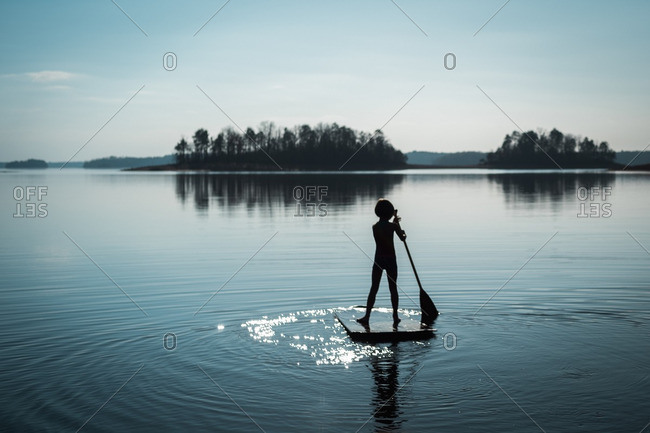 Silhouette of a little girl on a paddleboard
