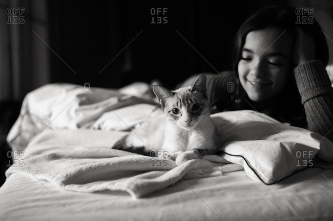 Girl petting a cat in black and white