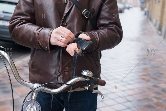 Man with bicycle plugging headphones into his cell phone