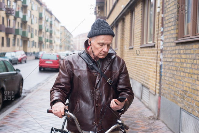 Man with bicycle listening to music on his cell phone