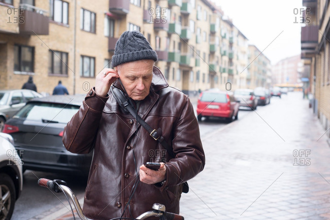 Man wearing leather jacket with bicycle listening to music on his cell phone