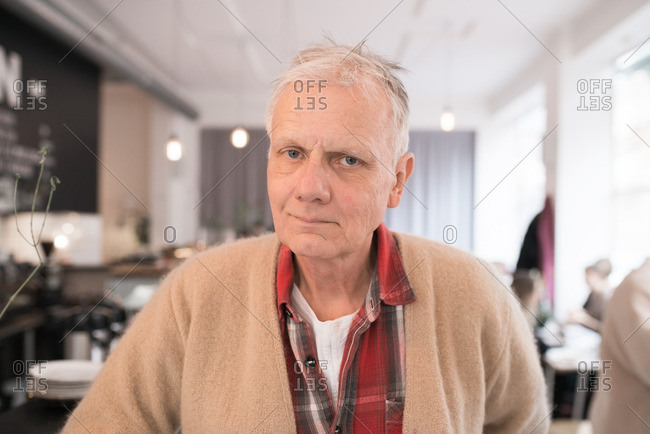 Portrait of a senior man wearing a tan sweater and plaid shirt
