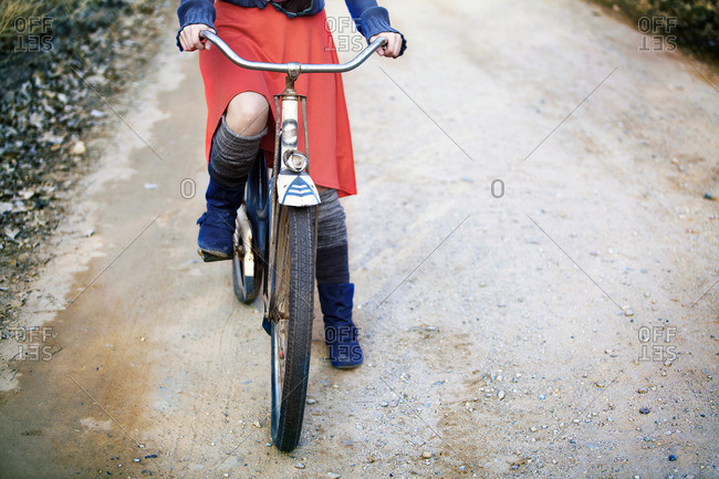 Girl riding bicycle on a dirt road