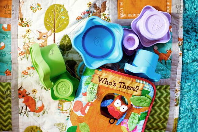 Colorful children's toys and book on a blanket