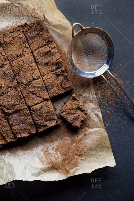 Brownies sprinkled with cocoa powder on parchment paper