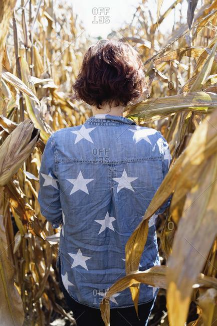 Woman wearing star shirt standing in a cornfield