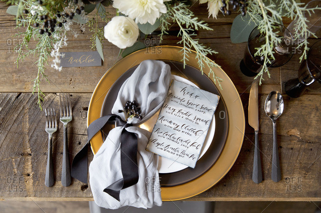 Place setting with menu on a rustic wooden table
