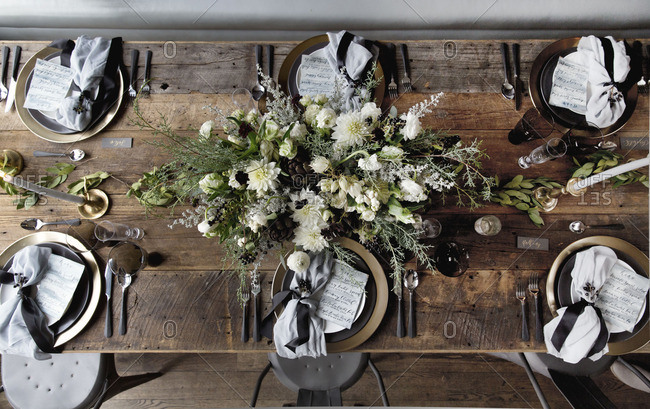 Place settings on a rustic wooden table with menus