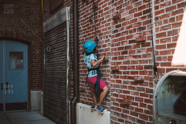 Young boy scaling a brick wall