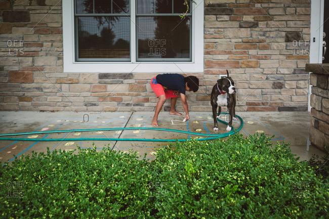 Boy drawing on sidewalk with chalk by his dog