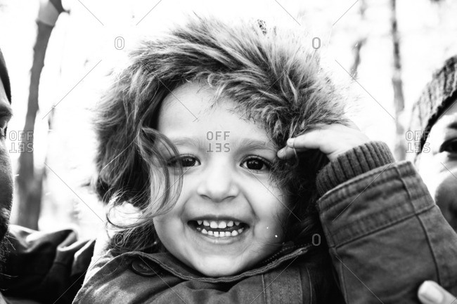Portrait of a happy little girl wearing furry hood in black and white