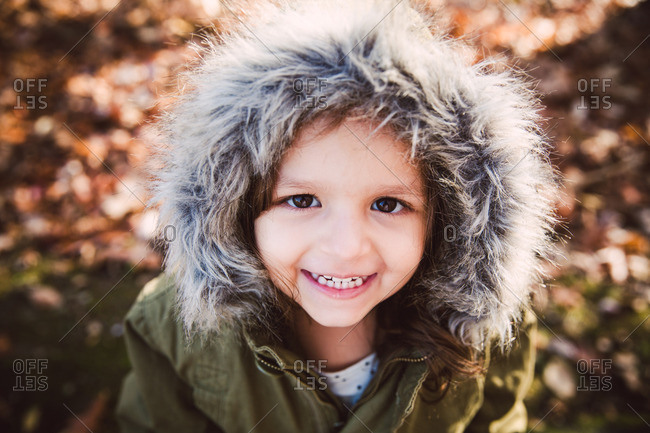 Portrait of a happy little girl wearing furry hood