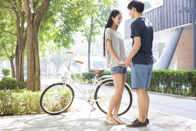 Young couple dating at campus with bicycle