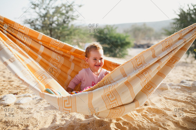 A girl sitting on a hammock and smiling
