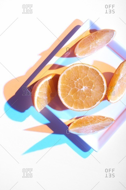 Orange slices arranged on a square plate and lit in a progressive modern style resulting in blue and orange shadows.