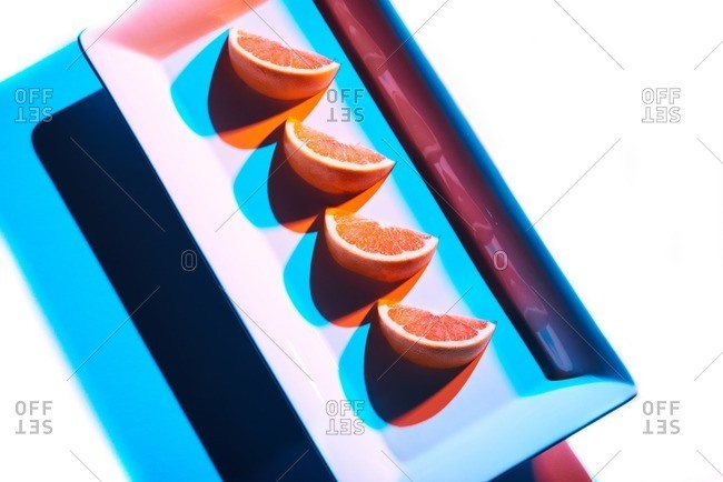 Slices of citrus an a rectangular plate and white background lit in a progressive modern style resulting in blue and orange shadows.