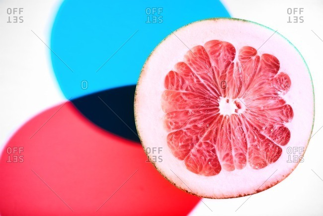 Pomelo shot in a modern progressive style resulting in two shadows, a blue and a red