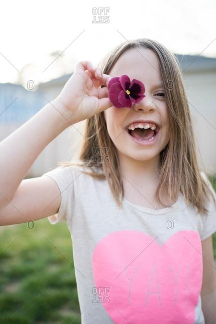 Girl holding flower over face