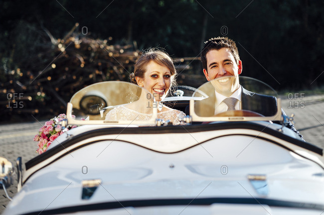 Couple posing in a bridal car after their wedding in Salamanca, Spain