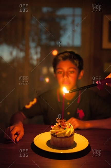 Boy sitting in front of a candle being lit on a birthday cupcake