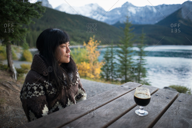Woman camper enjoys glass of beer and view of mountain lake at sunset