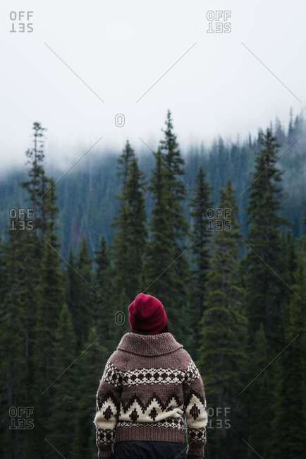 Woman looking up at misty clouds covering mountains above evergreen forest