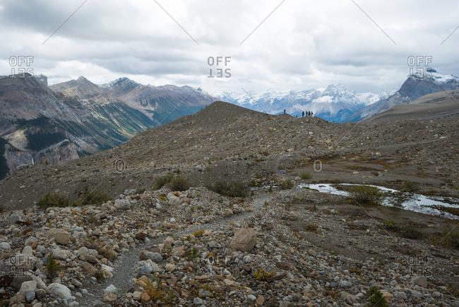 Rocky mountain trail in alpine zone under cloudy sky