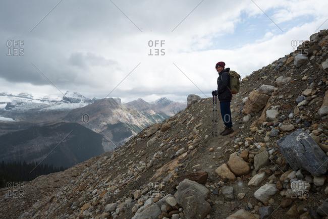 Lone female hiker traverses rocky mountain trail in alpine zone under cloudy sky