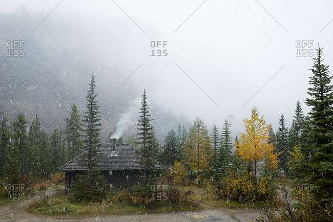 Smoke rises from cooking shack under foggy fall sky