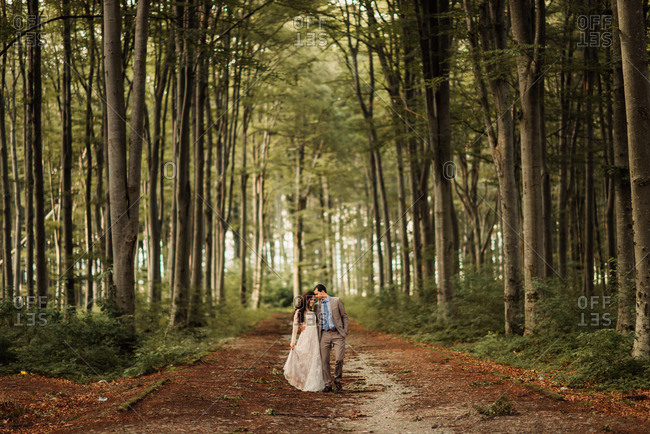 Bridal couple walking a forest path