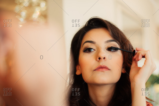 A bride putting on her mascara
