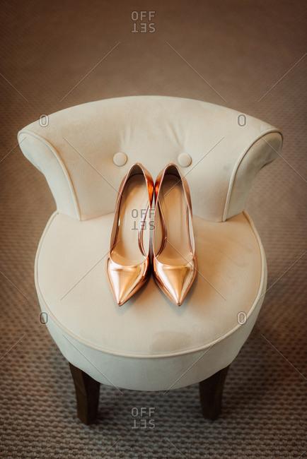 Golden high heels in a chair