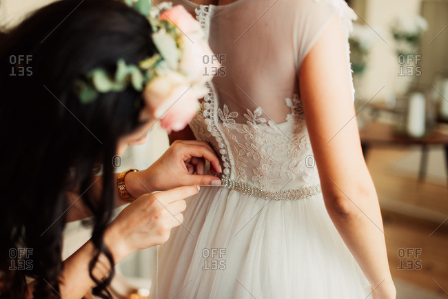 Woman helping bride button dress