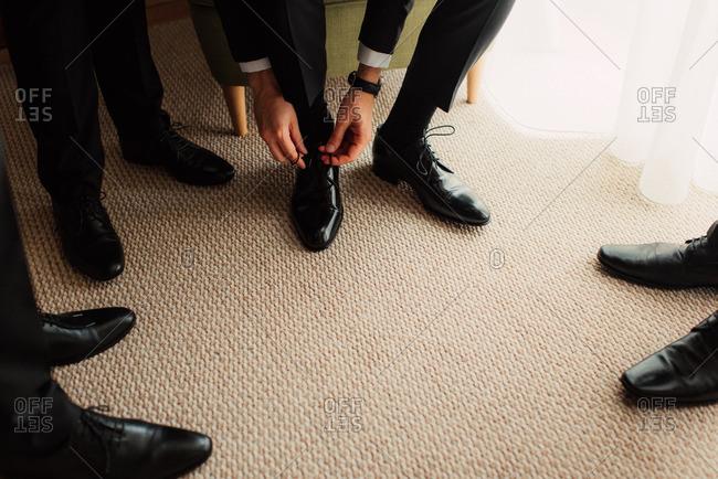 Groom tying shoe by groomsmen