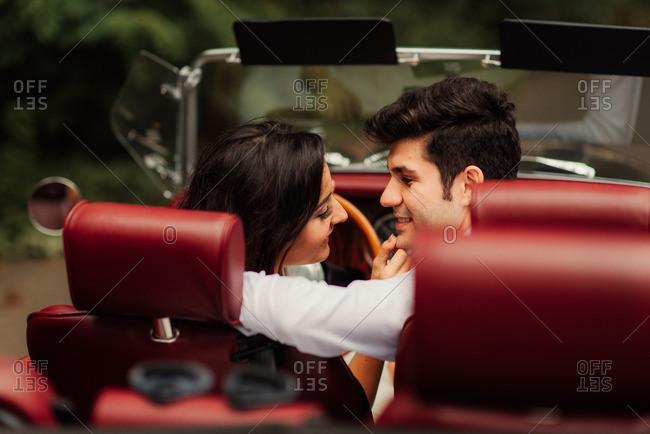 Bridal couple gazing lovingly in car
