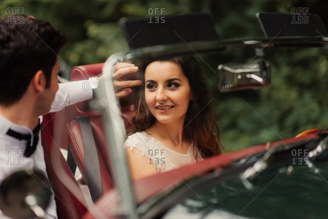 Bride looking at groom in car