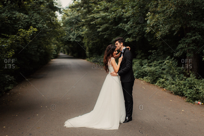 Man kissing bride on a rural road