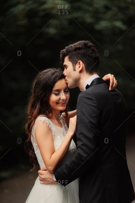 Man kissing bride on rural road