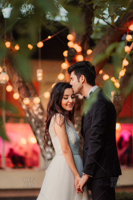 Groom kissing bride in romantic setting