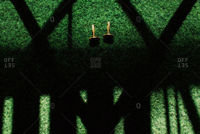 Pair of cufflinks on green background with shadows
